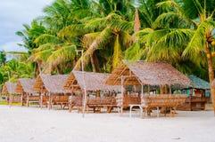 夏天遮光罩和竹扶手椅子在热带白色沙子靠岸 免版税库存照片