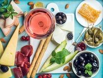 夏天酒快餐集合 玻璃上升了,肉、乳酪、橄榄、蜂蜜、面包条、坚果、雀跃和莓果与白色 库存图片