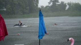 夏天雨,雷暴,在一个空的海滩的重的降雨量,偏僻的沙滩伞站立,猛烈,强劲的风,  股票视频