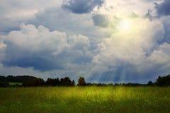夏天领域和日落与雨云 免版税库存照片