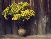 夏天领域黄色在木老背景的一个老水罐开花 库存图片