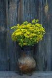 夏天领域黄色在木老背景的一个老水罐开花 免版税库存图片