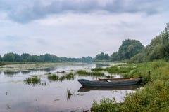 夏天风景:有小船的,用云彩盖的天空一条河 免版税图库摄影
