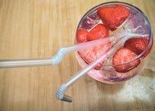 夏天饮料用在一块玻璃的草莓与两秸杆 库存图片