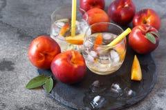 夏天饮食冷的饮料:两杯戒毒所纯净的水用油桃 库存照片