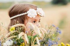夏天麦田的逗人喜爱的小女孩 有野花花束的一个孩子在他的手上 关闭,画象 免版税库存照片