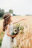 夏天麦田的逗人喜爱的小女孩 有野花花束的一个孩子在他的手上 库存照片