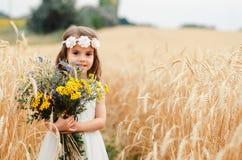 夏天麦田的逗人喜爱的小女孩 有野花花束的一个孩子在他的手上 免版税库存照片