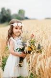 夏天麦田的逗人喜爱的小女孩 有野花花束的一个孩子在他的手上 图库摄影
