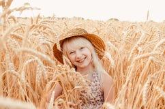 夏天麦田的逗人喜爱的小女孩 有麦子花束的一个孩子在他的手上 图库摄影