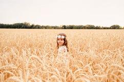 夏天麦田的逗人喜爱的小女孩 有麦子花束的一个孩子在他的手上 库存照片
