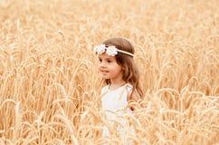 夏天麦田的逗人喜爱的小女孩 有麦子花束的一个孩子在他的手上 库存图片