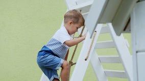 夏天,在庭院,孩子,一个四岁的男孩攀登在操场的儿童` s台阶 家庭花费 影视素材