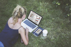 夏天,背面图,说谎在草坪和使用有图表、图和图的年轻女实业家膝上型计算机在屏幕上 库存图片