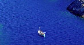夏天:在十字架的海角小海湾的一条水手小船在有蓝色海的西班牙 库存图片