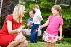 夏天:妈妈教女孩拿着闪烁发光物 库存照片