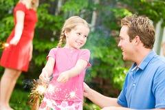 夏天:爸爸教女孩使用闪烁发光物 免版税库存图片