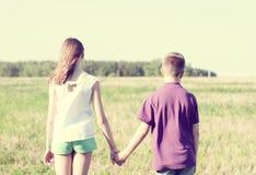 夏天晴天公园有握手的女孩的立场男孩享受自然,草甸,乐趣小小的家庭关系 免版税库存图片