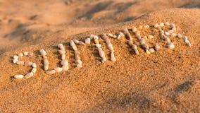 夏天 小小卵石写的词在一个沙滩 免版税库存照片