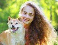 夏天画象愉快的可爱的女孩和狗 免版税图库摄影