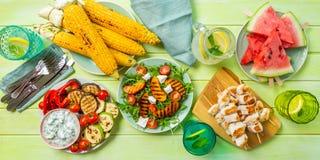 夏天bbq党概念-烤鸡,菜,玉米,沙拉,顶视图 库存照片