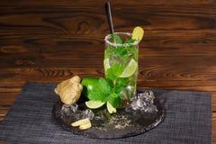 夏天mojito鸡尾酒用兰姆酒,新鲜的石灰,薄菏,击碎了冰、姜和阳桃在木背景 复制空间 库存照片
