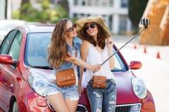 夏天selfie两美丽的女朋友临近汽车 库存图片