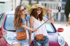 夏天selfie两美丽的女朋友临近汽车 免版税库存图片