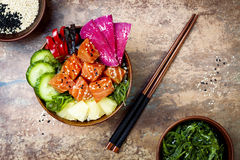 夏威夷三文鱼戳有海草、西瓜萝卜、黄瓜、菠萝和芝麻籽的碗 复制空间 图库摄影