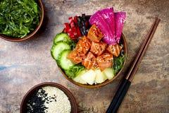 夏威夷三文鱼戳有海草、西瓜萝卜、黄瓜、菠萝和芝麻籽的碗 复制空间 免版税图库摄影