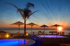夏时:在游泳池周围的美好的黎明与棕榈和遮阳伞, 免版税库存图片