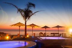夏时:红色黎明美丽的景色在游泳池周围的与棕榈 库存图片