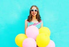 夏令时!愉快的微笑的妇女和空气五颜六色的气球 库存照片