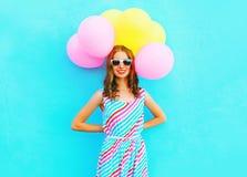 夏令时!愉快的微笑的妇女在手上拿着空气五颜六色的气球 免版税图库摄影