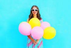 夏令时!愉快的微笑的少妇拿着空气五颜六色的气球 免版税图库摄影