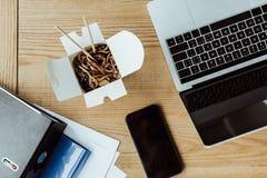 外卖面条顶视图午餐、商业文件、膝上型计算机和智能手机的有在木桌上的黑屏的 库存照片