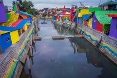 外南梦,印度尼西亚:从有五颜六色的房子的桥梁看的水道在双方,迷人的邻里,多云 免版税库存照片