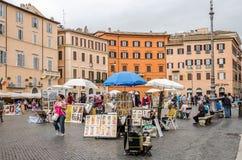 外国漫步在旅行的游人和本机在街道艺术家之间工作画象的在历史的广场Navo之间 免版税库存图片