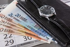 外国钞票、钱包和手表在桌上 图库摄影