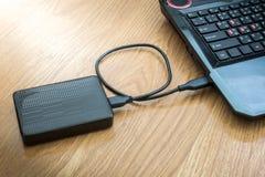 外在硬盘被连接到膝上型计算机 免版税库存照片