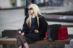 黑外套和太阳镜的美丽的年轻时髦的白肤金发的妇女有购物袋的坐一条长凳在公园 库存照片
