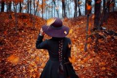 外套和帽子的,染黄的叶子背景,后面看法年轻时髦的女孩 免版税库存图片