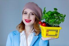 外套和贝雷帽的妇女有草本篮子的  免版税库存图片