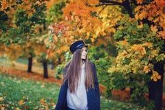 外套和黑帽会议的愉快的年轻女人 免版税库存照片