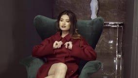 外套的一个女孩为坐在椅子的摄影师摆在 拍摄外套的编目的 股票视频
