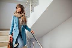 外套的女商人步行沿着向下在购物中心的台阶的 购物 方式 图库摄影