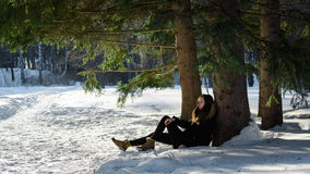 黑外套的女孩坐被解冻的补丁在雪的一棵树在一个美妙的狂放的森林里 库存图片