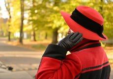 外套的妇女在秋天街道上花费半转动并且拿着用手一个黑红色帽子 图库摄影