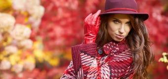 外套的妇女有帽子的和围巾在秋天停放 免版税图库摄影