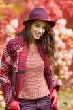 外套的妇女有帽子的和围巾在秋天停放 免版税库存照片